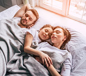 The daughter and parents sleeping under the blanket
