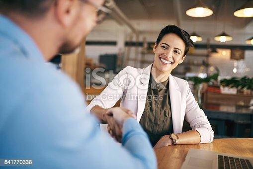 Shot of a man and woman shaking hands during a meeting in a coffee shop