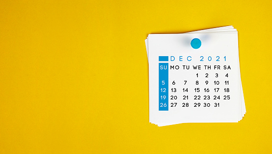 The December 2021 calendar is pinned on a yellow background. Horizontal composition with copy space.