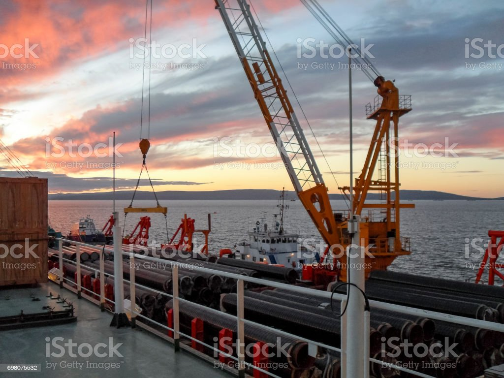 The deck lay barge. Pipes and Lifting cranes on the ship. Equipment for laying a pipeline on the seabed stock photo