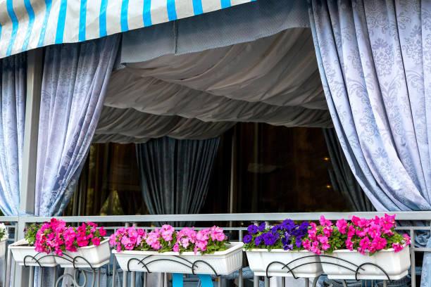 das dekor wird mit textilien an der decke und in form von gardinen mit blumentöpfen blüten drapiert. - garagen pergola stock-fotos und bilder