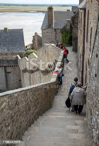 Le Mont-Saint-Michel, France - September 13, 2018: The defensive walls of Mont Saint Michele, having a broad top with a walkway and typically a stone parapet. Normandy, France