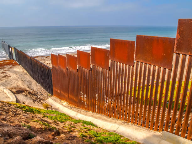 The degraded iron wall on the US-Mexico border in Tijuana Beach in northern Mexico Tijuana, Mexico, Nov 09 - A view from the Mexican side of the steel wall on the border between the United States and Mexico on the Pacific coast of Tijuana. In the background the Imperial Beach in US territory. frontier field stock pictures, royalty-free photos & images