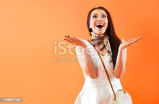 1045527172 istock photo The delight and surprise of a beautiful woman. Girl hands up and rejoices. Expression of emotion. 1208817307