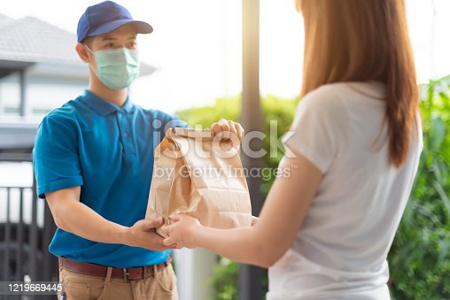 istock The delivery man is delivering the paper bag to beautiful female customer in front of the home. 1219669445