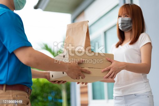 istock The delivery man is delivering the paper bag to beautiful female customer in front of the home. 1219669449