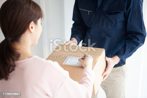 istock The delivery member hands the cardboard box to the woman. 1129528857