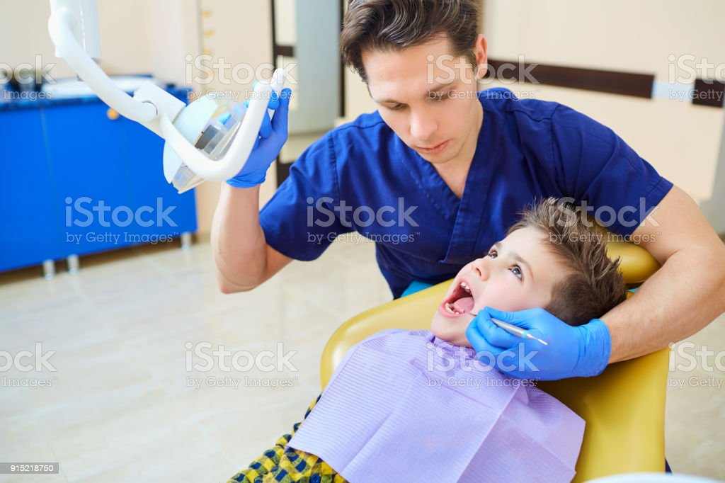The dentist checking the teeth of  boy teenage stock photo