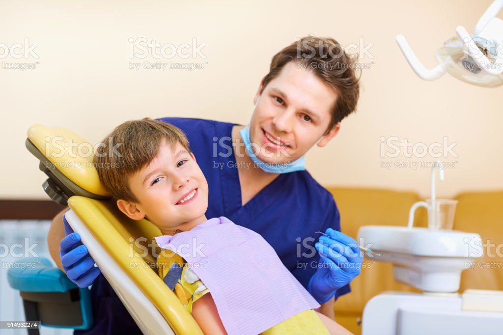 The dentist checks the teeth of a man boy teenager stock photo