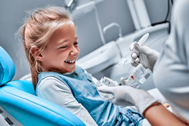 The dentist tells the child about oral hygiene and shows an artificial jaw and toothbrush stock photo