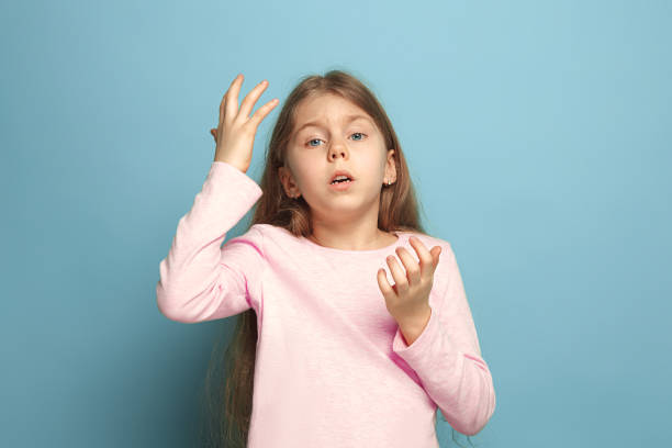 the deplorable girl. teen girl on a blue background. facial expressions and people emotions concept - deplorable stock pictures, royalty-free photos & images