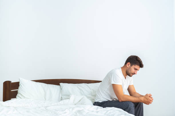 The depressed man sitting on the bed on the white background The depressed man sitting on the bed on the white background erectile dysfunction stock pictures, royalty-free photos & images
