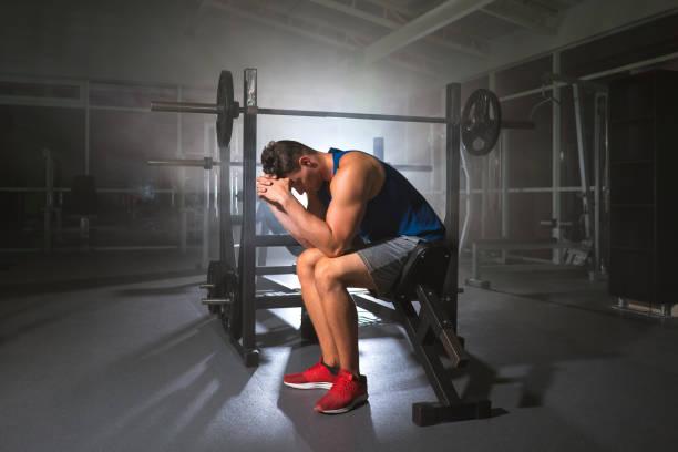 der depressive sportler sitzt im sportzentrum - mit muskelkater trainieren stock-fotos und bilder