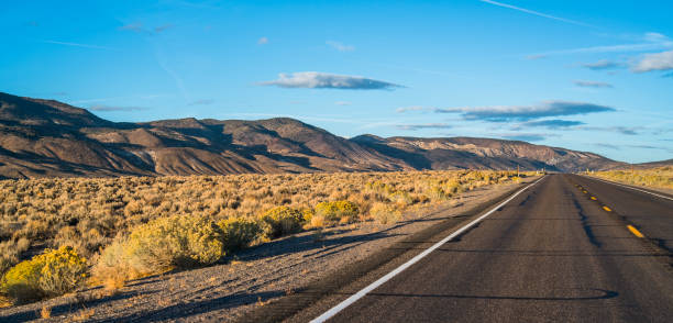 The desert highway in Nevada at sunset stock photo