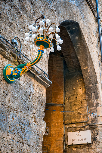 The detail of a lamppost with the colors of the 'Contrada del Bruco' in the heart of Siena