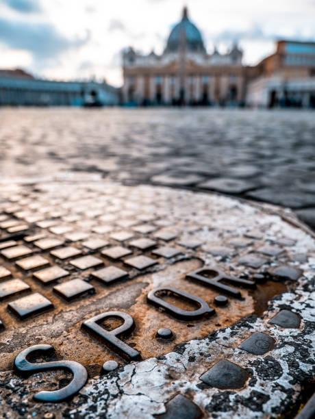 Le détail d'une couverture de trou d'homme avec l'inscription SPQR sur la place de la Basilique Saint-Pierre - Photo