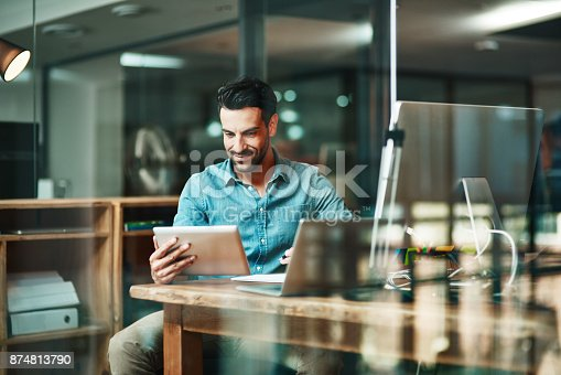 Shot of a young businessman using a digital tablet at his desk in a modern office