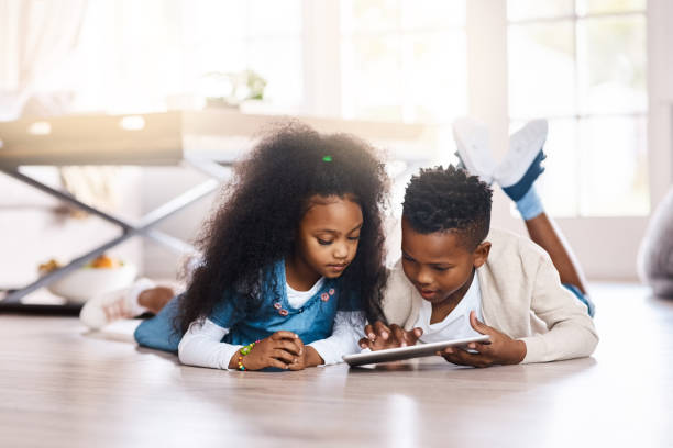 The digital world answers to their curiosity Shot of two adorable little siblings using a digital tablet together at home touchpad stock pictures, royalty-free photos & images