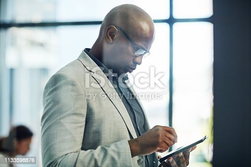 Shot of a mature businessman working on a digital tablet in an office