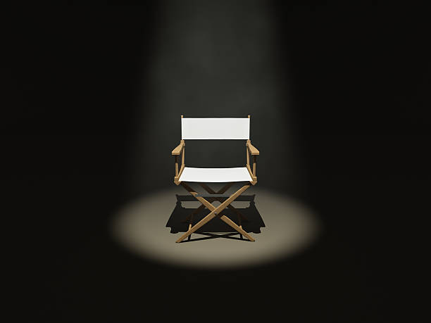 The Director (Front) Front side of a wooden / white director's chair under the spot light. director stock pictures, royalty-free photos & images