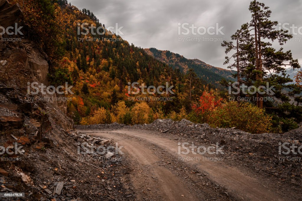The dirt road strewn with rocks on the background of Georgian forested mountains. stock photo