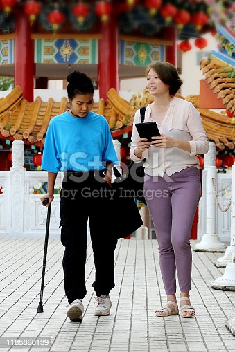 A mixed ethnicity young lady is visiting Chinese temple, Thean Hou in Kuala Lumpur Malaysia while chatting with local people cheerfully.