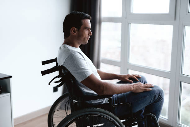 The disabled person in a wheelchair sits in front of a large panoramic window and looks into it. The disabled person in a wheelchair sits in front of a large panoramic window and looks into it. He is sad. He is in the living room of his modern apartment. paralysis stock pictures, royalty-free photos & images