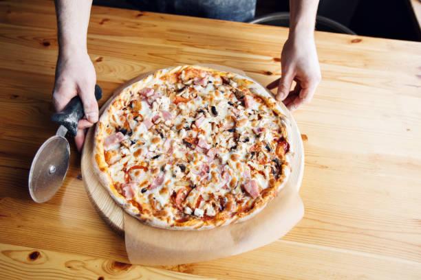 die disc-messer schneidet. hausgemachte pizza mit schinken, champignons, mozzarellail. koch in schürze - ofengemüse mit feta stock-fotos und bilder
