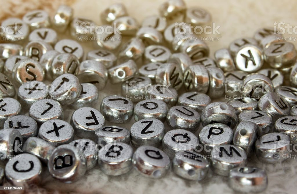 The discarded alphabet of beads on cloth stock photo