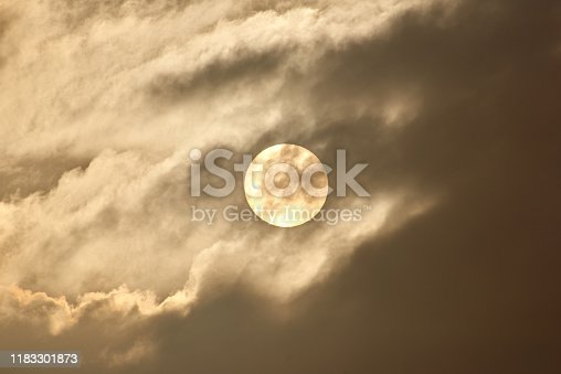 The disk of the sun shines through the clouds and fog.