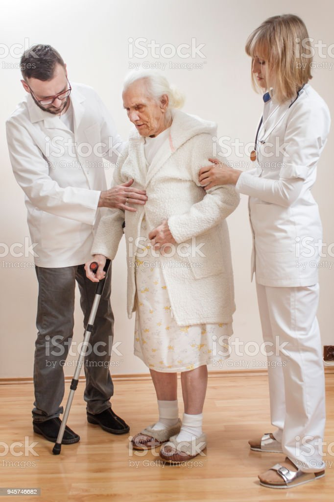 The doctor and the nurse belay and help the old woman in a dressing gown and nightgown supporting her with a cane. stock photo