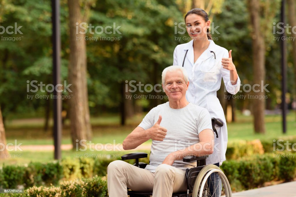 The doctor and the patient who is sitting on the wheelchair hold their thumbs up and smile Thumbs up. An elderly patient who is sitting in a wheelchair and a young woman doctor behind him are holding his thumbs up and smiling Adult Stock Photo