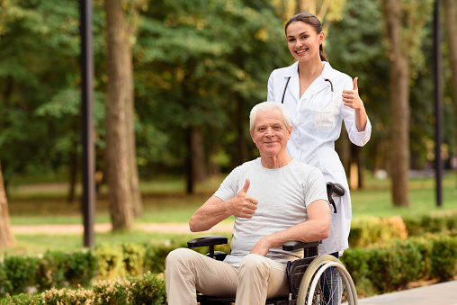 The Doctor And The Patient Who Is Sitting On The Wheelchair Hold Their Thumbs Up And Smile Stock Photo - Download Image Now