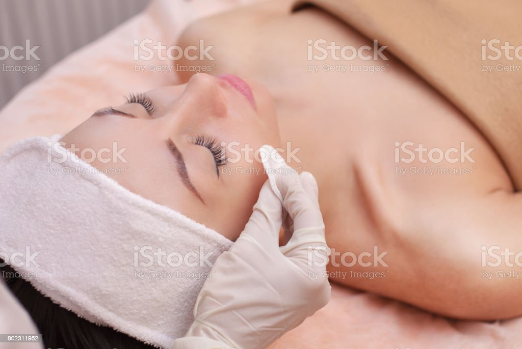 The doctor cosmetologist cleanses with a tonic the face skin of a beautiful, young woman stock photo