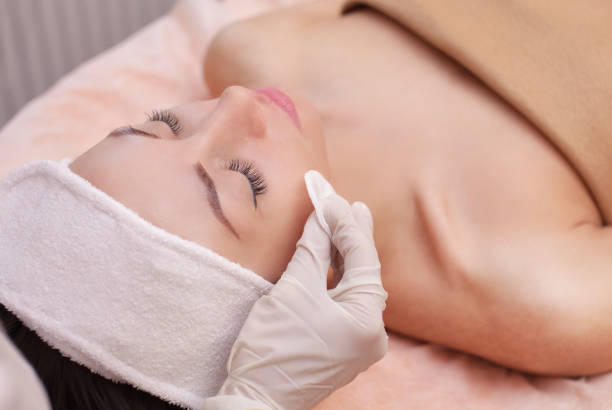 the doctor cosmetologist cleanses with a tonic the face skin of a beautiful, young woman - beautician stock photos and pictures