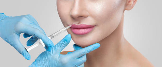 The doctor cosmetologist makes Lip augmentation procedure of a beautiful woman in a beauty salon.Cosmetology skin care. stock photo
