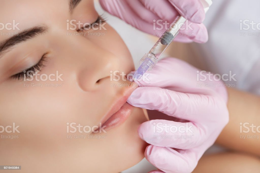 The doctor cosmetologist makes Lip augmentation procedure of a beautiful woman in a beauty salon stock photo