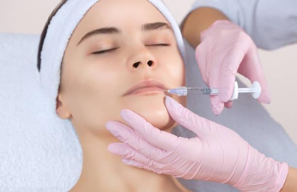 der arzt kosmetikerin macht lippe brustvergrößerung verfahren von einer schönen frau in einem schönheitssalon. - nadeldesigns stock-fotos und bilder