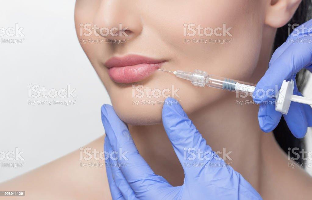 La cosmetóloga médico hace que procedimiento de aumento de labios de una mujer hermosa en un salón de belleza. - foto de stock