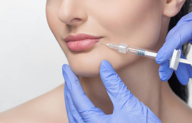 The doctor cosmetologist makes Lip augmentation procedure of a beautiful woman in a beauty salon. The doctor cosmetologist makes Lip augmentation procedure of a beautiful woman in a beauty salon.Cosmetology skin care. injecting stock pictures, royalty-free photos & images