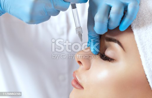 istock The doctor cosmetologist makes prick in the nose to correct the hump of a beautiful woman in a beauty salon. 1129880255
