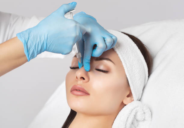 The doctor cosmetologist makes prick in the nose to correct the hump of a beautiful woman stock photo
