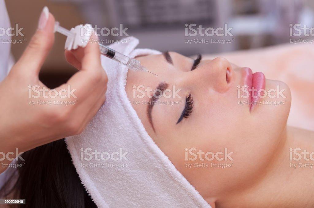 De arts schoonheidsspecialist maakt de Botulinotoxin injectie procedure voor aanscherping en gladstrijken van rimpels op de huid van het gezicht van een mooie, jonge vrouw in een schoonheidssalon foto