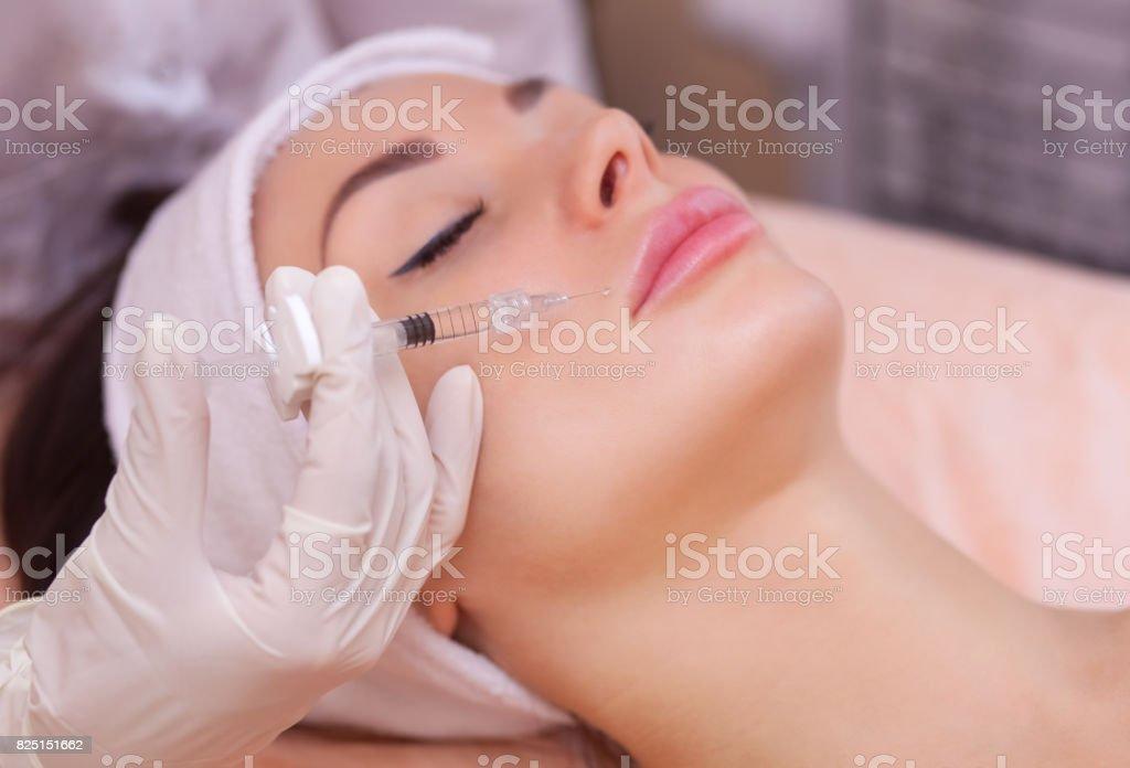 La cosmetóloga doctor hace el procedimiento de inyección Botulinotoxin para apretar y alisar las arrugas en la piel de la cara de una mujer joven, hermosa en un salón de belleza - foto de stock