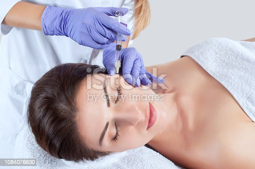 istock The doctor cosmetologist makes the Rejuvenating facial injections procedure for tightening and smoothing wrinkles on the face skin of a beautiful, young woman in a beauty salon 1084076630
