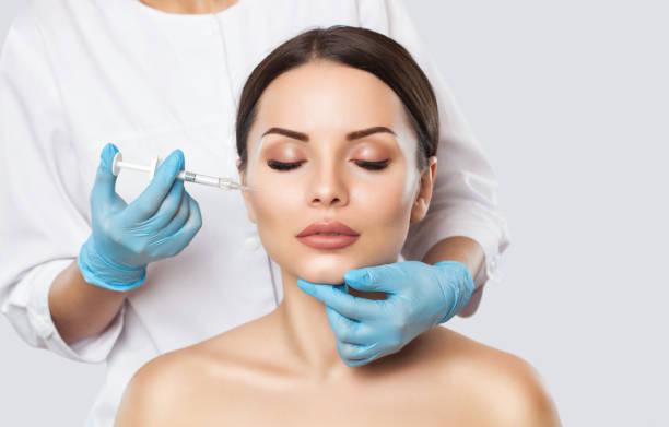 Der Arzt Kosmetikerin macht das 3.rejuvenating Gesicht Spritzen Verfahren zur Straffung und Glättung von Falten im Gesichtshaut eine schöne, junge Frau in einem Schönheitssalon. – Foto