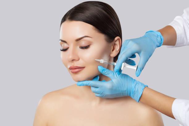 Die Ärztin Kosmetologe macht die Verjüngung Gesichtsspritzen Verfahren zum Straffen und Glätten Falten auf der Gesichtshaut einer schönen, jungen Frau – Foto