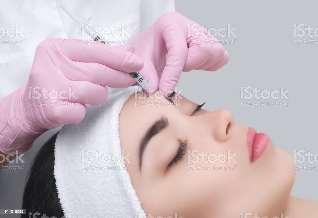 De arts schoonheidsspecialist maakt de Rejuvenating gezicht injecties procedure voor aanscherping en gladstrijken van rimpels foto