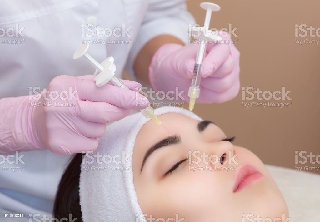 The doctor cosmetologist makes the Rejuvenating facial injections procedure for tightening and smoothing wrinkles stock photo