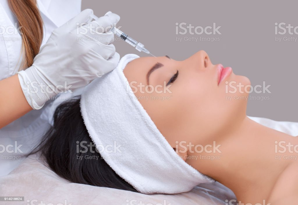 The doctor cosmetologist makes the Rejuvenating facial injections procedure for tightening and smoothing wrinkles on the face skin stock photo